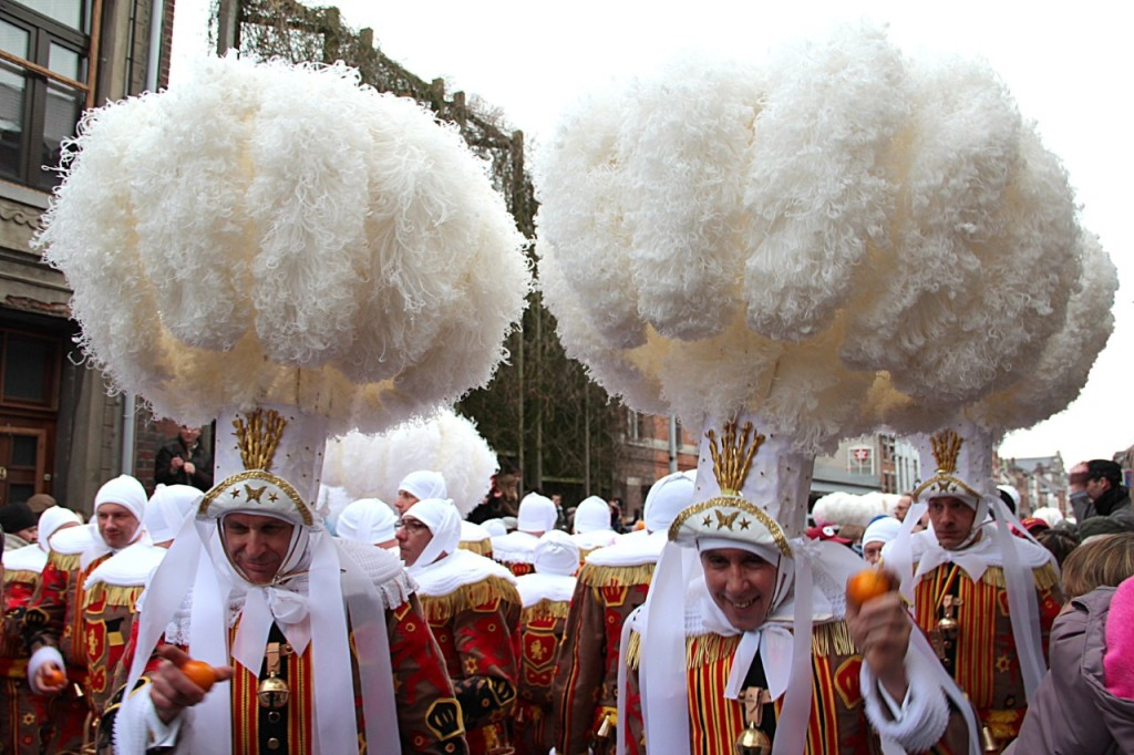 Men dressed as Gilles with ostrich feathers