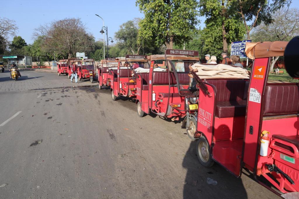 A line of pink rickshaws